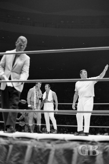 A lei draped Don Leo Jonathan chats with Nick Bockwinkel as announcer Jim Lathrop leaves the ring before the start of the match