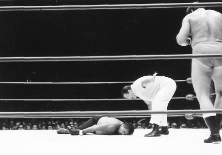 Referee Pete Peterson counts Curtis Iaukea on the mat